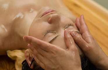 young woman on the ayurvedic aromatherapy oil massage procedure